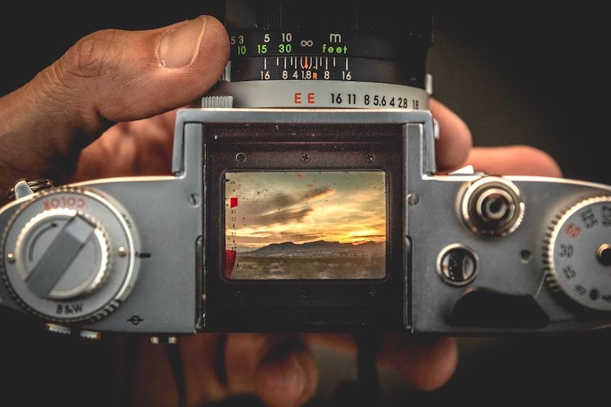 Hand holding a manual 35mm SLR camera