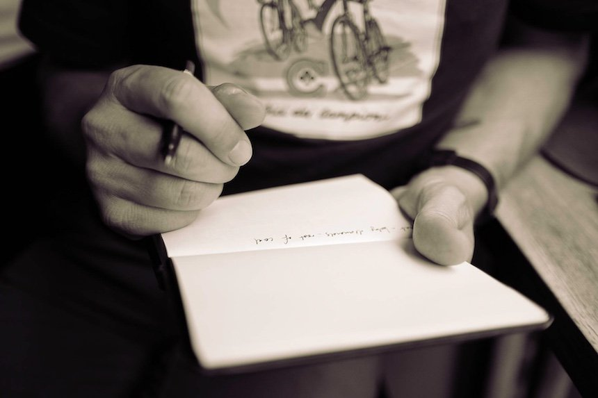 Man writing in a notebook with a pen. (Photo by Calum MacAulay.)