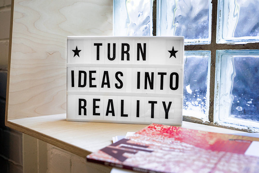A sign with the words 'Turn Ideas into Reality.' (Photo by Mika Baumeister.)