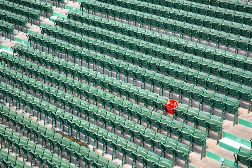 Photo of one red chair among hundreds of green ones by Veronica Benadvides