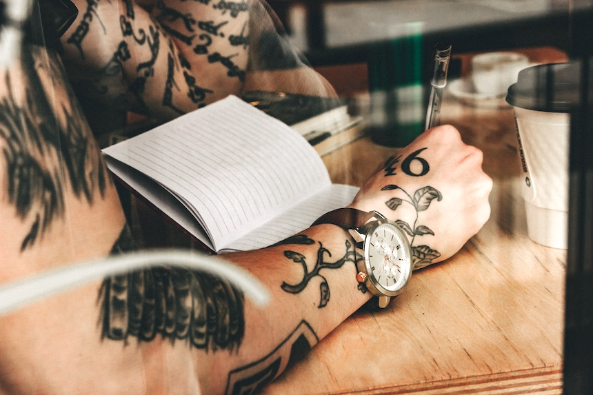 Tattooed person writing in a notebook in a cafe